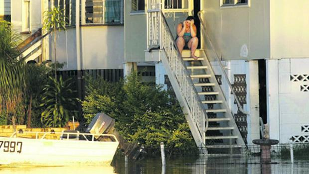 A woman uses her mobile phone as she sits on the stairs of her house, which is partially submerged in floodwaters in Rockhampton, Queensland