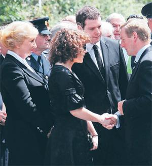 Mr Lenihan's wife Patricia and children Claire and Tom are comforted by Taoiseach Enda Kenny