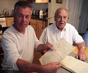 Kevin Keogh and his father Kevin senior with his grandfather Michael Keogh's handwritten notes from his time in prison camps in Germany during World War 1