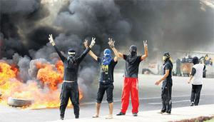 Anti-government protesters flash victory signs as they burn tyres in Budaiya, west of Manama, yesterday.