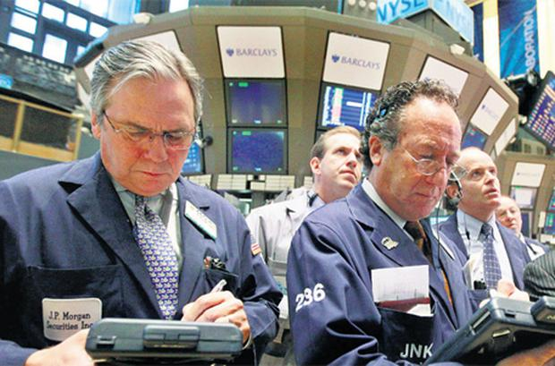 Traders work on the floor of the New York Stock Exchange yesterday where shares fell on weaker jobs data. Photo: Reuters