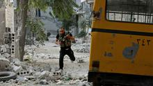 A Free Syrian Army fighter runs to take cover from a sniper in Aleppo's Bustan al-Basha district. Photo: Reuters
