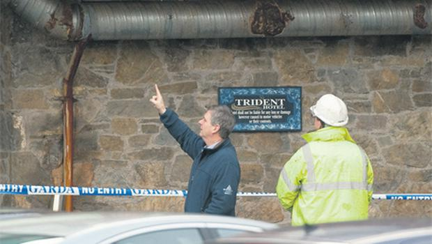 Members of the investigative team examine an external pipe directly under the bedroom wing of the Trident Hotel in Kinsale