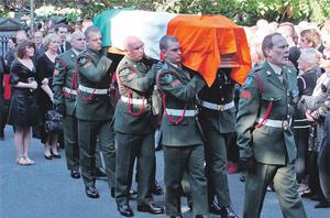 Brian Lenihan's remains are carried into St Mochta's church in Porterstown, Dublin, last night