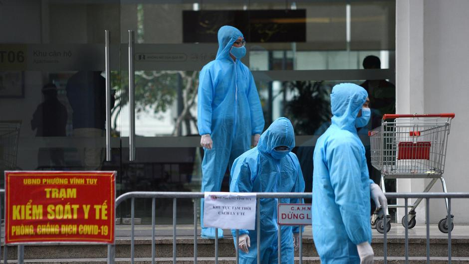 Medical workers in protective suits stand outside a quarantined building in Hanoi, Vietnam. Photo: Reuters/Thanh Hue