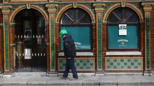 A man walks past a closed pub in Dublin's Temple Bar on St Patrick's Day. Photo: Peter Morrison/AP