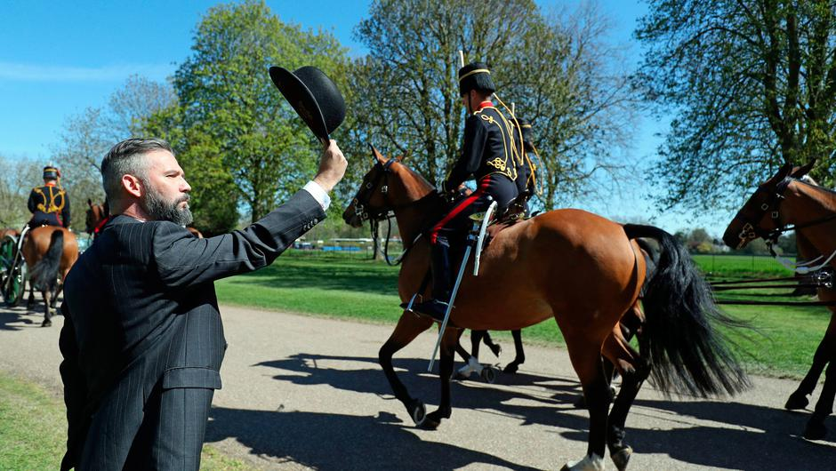 A man raises a bowler hat to the King's Troop Royal Horse Artillery as they ride past on the Long Walk, Windsor, ahead of the funeral of the Duke of Edinburgh taking place in St George's Chapel, at Windsor Castle, Berkshire, this afternoon. Picture date: Saturday April 17, 2021. PA Photo. See PA story FUNERAL Philip. Photo credit should read: Andrew Matthews/PA Wire