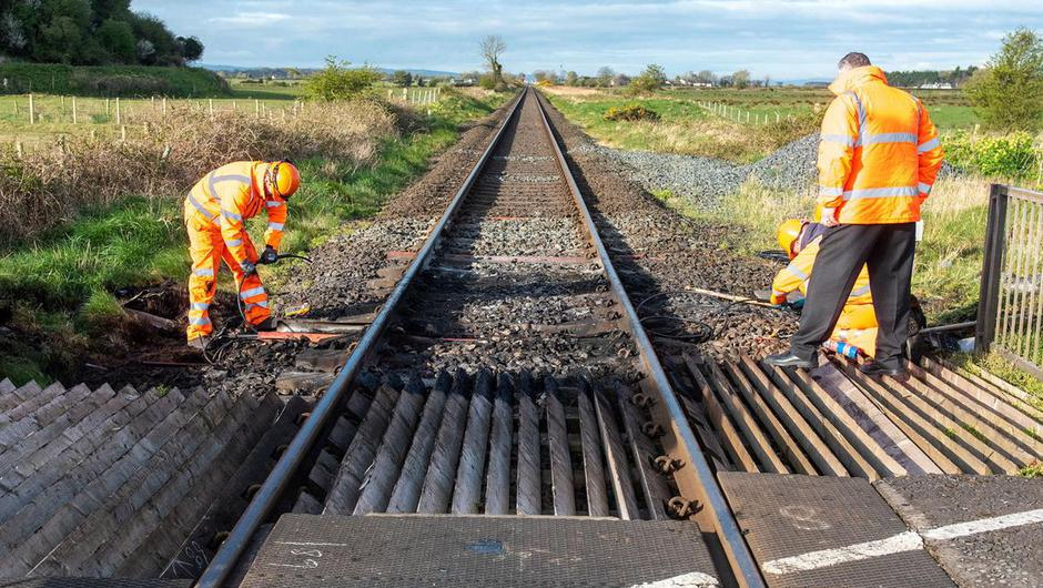 Engineers examine damage to the track at a level crossing outside Bellarena where a train was forced to make an emergency stop when a car was set on fire at the crossing. Photo: Martin McKeown.