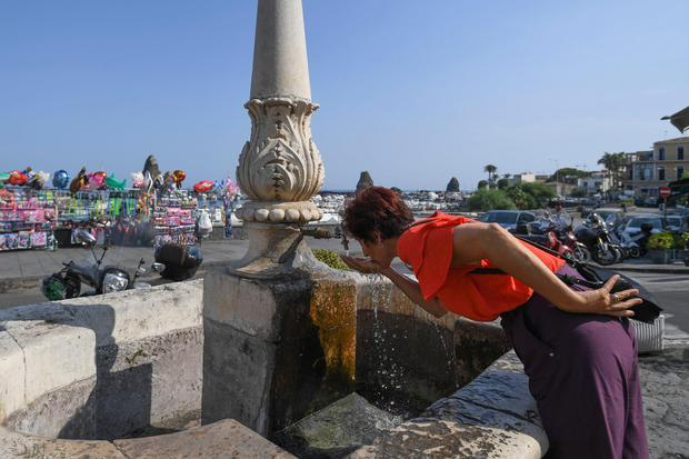 A woman refreshes herself at a fountain in Aci Trezza, near Catania, Sicily, Italy. Photo: AP