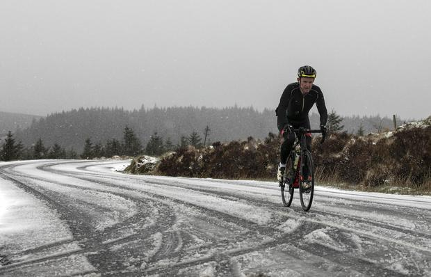 Tim McCormack cycles through a snow shower in Kilakee, County Dublin (Photo: Damien Eagers)