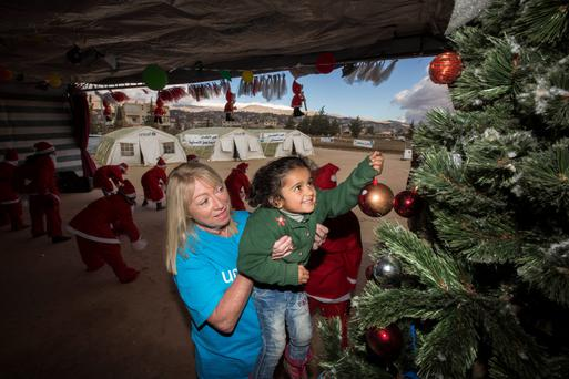 Unicef Goodwill Ambassador Anne Doyle decorates a Christmas tree, helped by Amina (4) in a Unicef centre in the Bekaa Valley, Lebanon