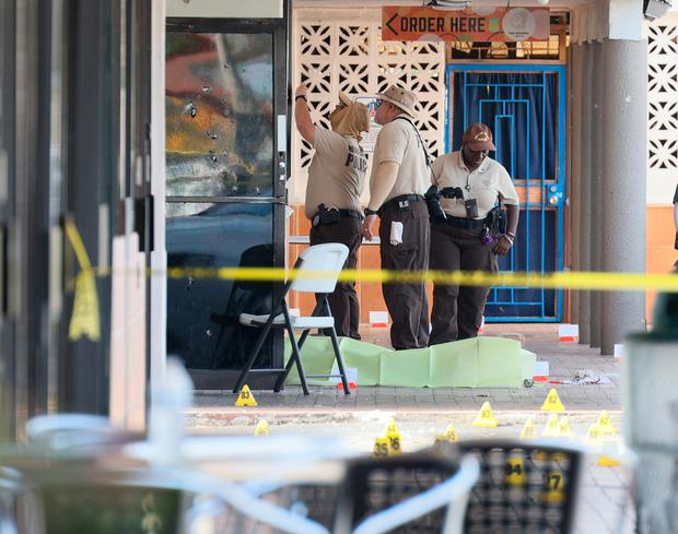 HIALEAH, FLORIDA - MAY 30: Miami-Dade police investigate near shell case evidence markers on the ground and a door with what appear to be bullet holes where a mass shooting took place outside of a banquet hall on May 30, 2021 in Hialeah, Florida. Police say that two people died, and an estimated 20 to 25 people are injured after the shooting at the banquet hall rented out for a concert. (Photo by Joe Raedle/Getty Images)
