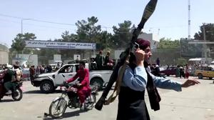 A Taliban fighter runs towards crowd outside Kabul airport, Afghanistan in this still image taken from a video. Photo: REUTERS TV/via REUTERS