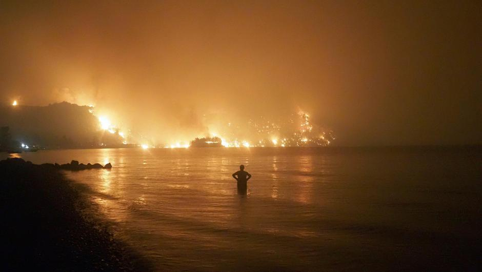 A man watches as wildfires approach Kochyli beach near Limni village on the island of Evia, about 160 kilometers (100 miles) north of Athens, Greece.