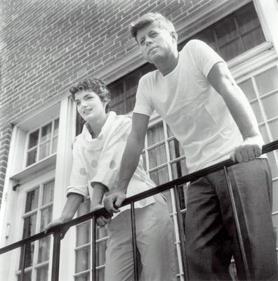 John and Jacqueline Kennedy look out from the balcony of their rented Georgetown townhouse in 1954