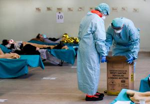 ITALIAN EXPERIENCE: Paramedics carry a hazardous medical waste box as patients lie on camping beds in an emergency structures set up at the Brescia hospital, Italy. Photo: Luca Bruno