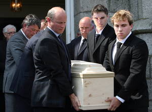 Sons Mathew and Danny carry the coffin of their father