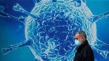 Not to be sneezed at: A man walks past an illustration of a virus outside a science centre in Oldham in Britain. PHOTO: REUTERS/PHIL NOBLE