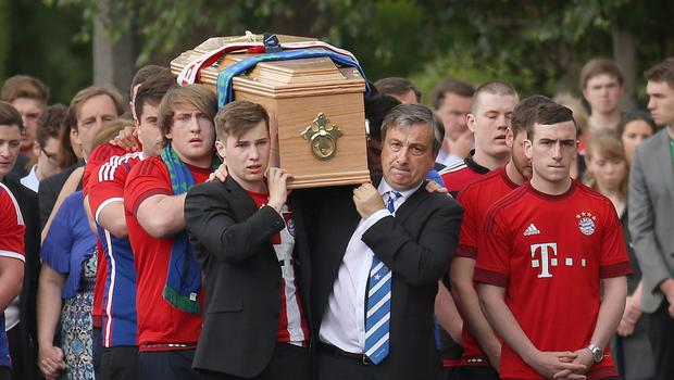 John Schuster, right, and Alexei, left, along with friends, carry the remains of Niccolai Schuster at his funeral in Dublin last week
