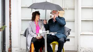 Brolly good: Seamus and Sue Watters from Crossmaglen refuse to let the rain spoil their day out as they enjoy a coffee in the rain on Berkeley Road in Dublin. PHOTO: FRANK McGRATH
