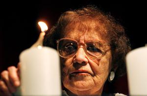 Auschwitz's survivor Lea Novera lights a candle while attending a ceremony during the International Holocaust Remembrance Day at the AMIA Jewish cultural centre in Buenos Aires .