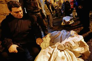 A man holds the hand of his dead son during the transfer of over a dozen of corpses from a hotel lobby to a local hospital following clashes with riot police at Independence Square in Kiev February 20, 2014.