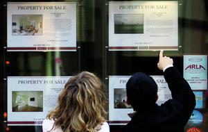 People view properties advertised for sale in the window of an estate agent
