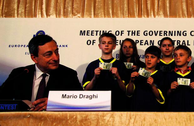 President of the European Central Bank Mario Draghi looks at school children holding the newly introduced 5 Euro banknotes after a news conference during the Meeting of the Governing Council of the European Central Bank in Bratislava.