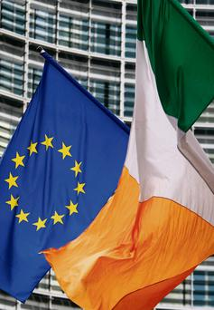 An Irish flag flies next to an EU flag in front of the EU Commission headquarters in Brussels