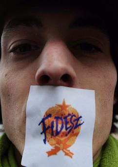 A protester wears a FIDESZ-sticker on his mouth to protest against the new Hungarian Constitution during an anti-government demonstration in front of the headquarters of the governing FIDESZ party in Budapest on March 30, 2013. The fourth modification of the basic law will be come into force on April 1. AFP PHOTO / ATTILA KISBENEDEKATTILA KISBENEDEK/AFP/Getty Images