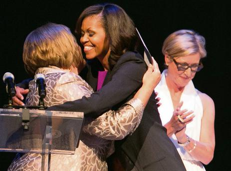 Michelle Obama is hugged by Fionnuala Kenny at the Gaiety Theatre, with Moya Doherty in the background