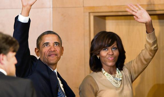 US President Barack Obama and his wife Michelle wave to the crowd in the Waterfront Hall in Belfast
