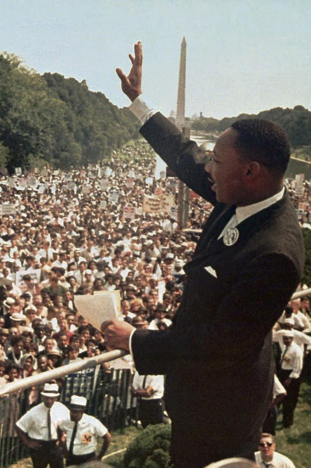 Martin Luther King waves to the crowd after his speech