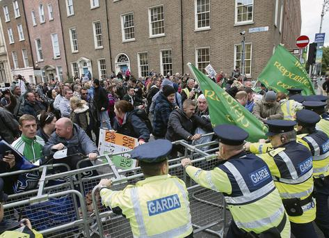 Gardai push against crowd barriers as protesters gather outside Leinster House in Dublin
