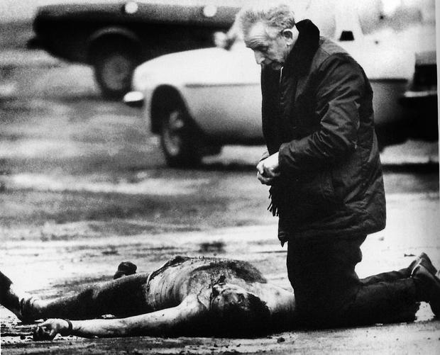 Fr Alec Reid prays over the body of one of the British Army corporals killed in Andersontown in March 1988.