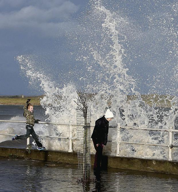 Waves crash on to the Coast Road in Malahide, Co Dublin, yesterday. Brian Lawless/PA Wire