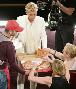 Host Ellen DeGeneres orders a pizza onstage during the Oscars and distributes it to celebrities in the front row. Photo: Kevin Winter