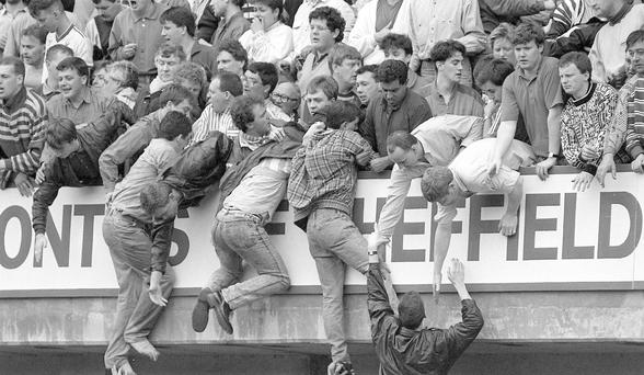 Liverpool fans at Hillsborough try to escape severe overcrowding during the Liverpool v Nottingham Forest FA Cup semi-final football match on April 15, 1989.