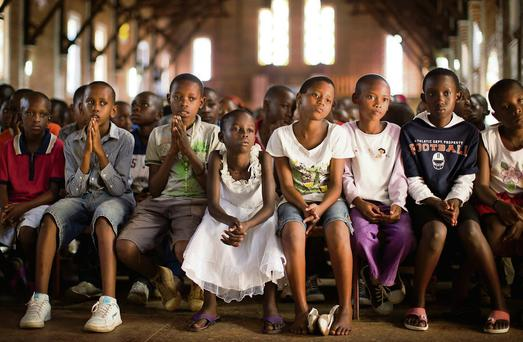 Rwandan children listen and pray during a Sunday morning service at the Saint-Famille Catholic church, the scene of many killings during the 1994 genocide, in the capital Kigali. Picture: Ben Curtis