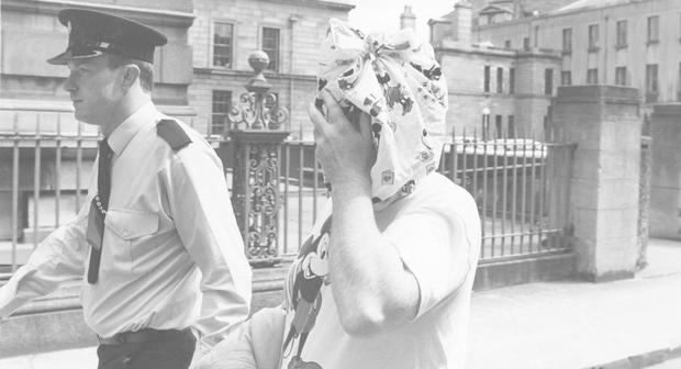 WATCHING BRIEF: Martin Cahill, 'The General', covers his face with a pair of Mickey Mouse boxers after leaving court in 1988. Photo: Mark Maxwell