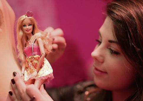A girl plays with a Barbie doll at a Berlin Toy Show. getty images