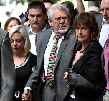 Rolf Harris, centre, outside court