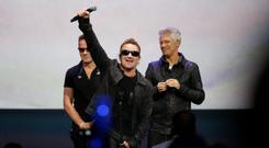 Bono (C) ofU2 gestures to the audience after performing at an Apple event at the Flint Center in Cupertino, California.
