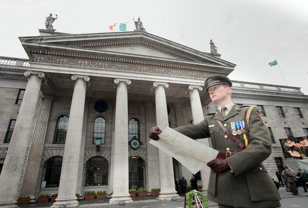 Captain Sean Coffey from Defence HQ reads the procamation during a Commemoration marking the 98th Anniversary of the 1916 Rising at the GPO on O' Connell Street, Dublin