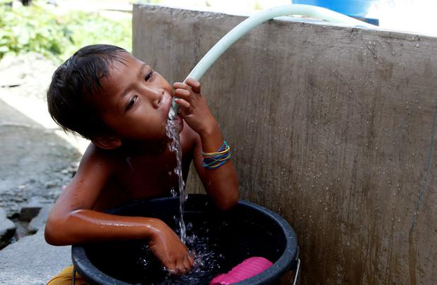 A boy drinks water from a hose outside bunkhouses for Typhoon Haiyan survivors, which were built by humanitarian agency ACF (Action Against Hunger) International, in Tacloban city in central Philippines