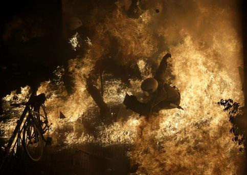 A riot police officer is engulfed by petrol bomb flames during protests in front of the parliament during clashes in Athens, Greece