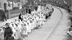Girls in their Holy Communion dresses lead a Corpus Christi procession in Dublin in 1965