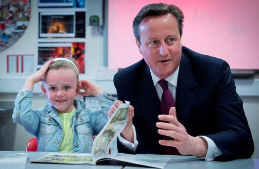 SCHOOL DAZE: David Cameron with six-year-old Lucy Howart at her school in Bolton. Photo: Stefan Rousseau/PA
