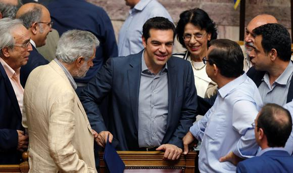 FLAWS: Greek Prime Minister Alexis Tsipras is congratulated by lawmakers after a voting session at the parliament in Athens, Greece, yesterday. The Greek parliament voted overwhelmingly in favour of authorising the left-wing government of Tsipras to negotiate with international creditors on the basis of a reform programme unveiled last week. Photo: Christian Hartmann