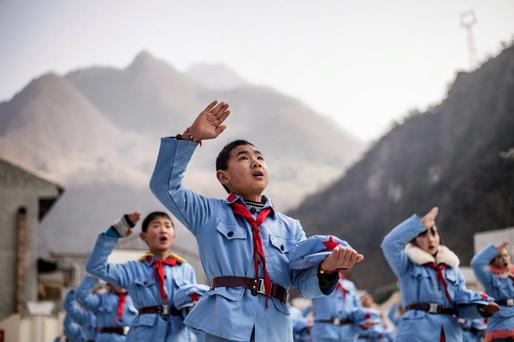 Children dressed in uniform sing after raising the national flag at the Beichuan Red army elementary school in Beichuan, southwest China's Sichuan province